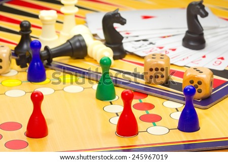 Photo shows a closeup of a various board games including chess and cards. - stock photo