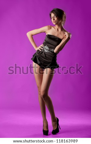 Photo slender girl with excellent adorable legs on the high heels posing in the studio on purple background - stock photo