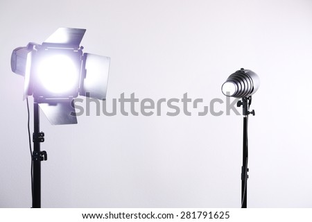 Photo studio with lighting equipment on white wall background - stock photo
