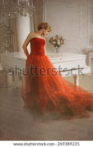 Photo stylized as old picture in which a woman in a red dress standing near a white grand piano head bowed. - stock photo
