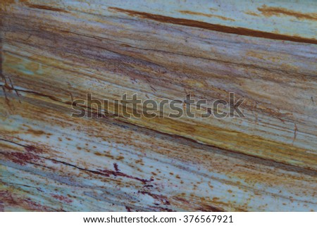 Photo texture of the stone surface with a unique pattern of bands of orange and brown shades. - stock photo