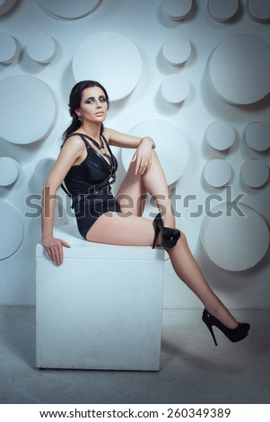 Photo Tinting in cool tones. Girl posing sitting on a cube in the studio. Shoes on his feet and long heels. On the belt wearing belt. - stock photo