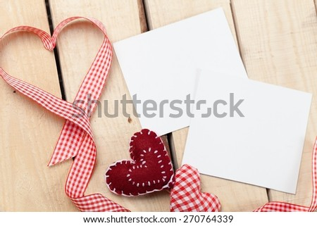 Photo. Two photo frames and small red candy heart on wooden background - stock photo