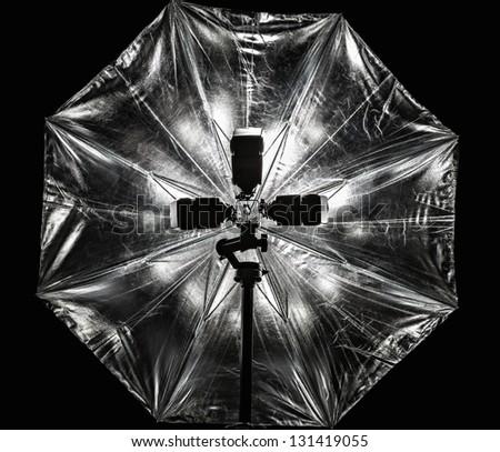 Photo umbrella and three flashes on black background - stock photo
