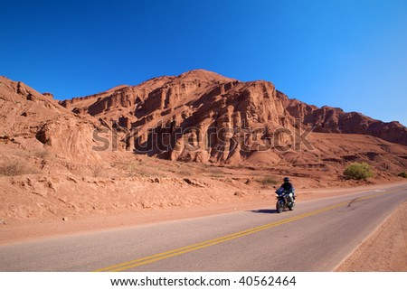 Photo unrecognizable person on a motorcycle. Motobikers on paved roads in the mountains of red against the blue, clear sky. - stock photo