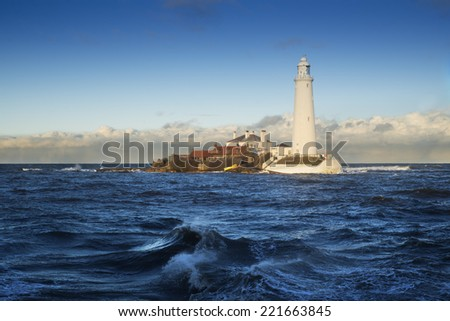 Photo was taken when high tide surge gave unusual perspective of St.Mary's island. I took grabbed this shot with dramatic clouds and waves, blue sky and momentarily peaked sun lit the lighthouse. - stock photo