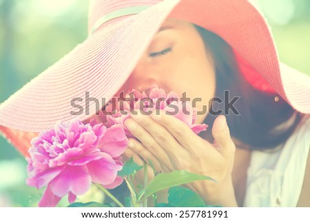 photo with artistic blurring and blur effect. special defocused effect. Vintage toning. film retro style. outdoor closeup portrait of a beautiful woman. lady in a hat in the park with flowers - stock photo