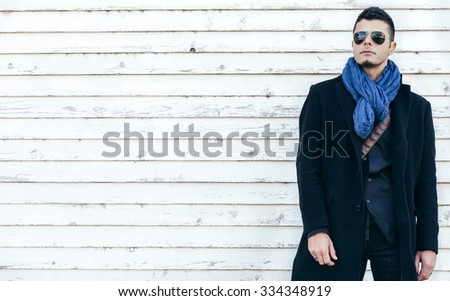 Photo with handsome man in coat on white wooden background with blank space,selective focus - stock photo
