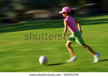Photo with motion blur effect of a young girl running with a ball - stock photo