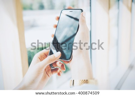 Photo woman holding modern smartphone in hands. Open space loft office. Reflection screen. Panoramic windows background. Horizontal mockup. Film effect - stock photo
