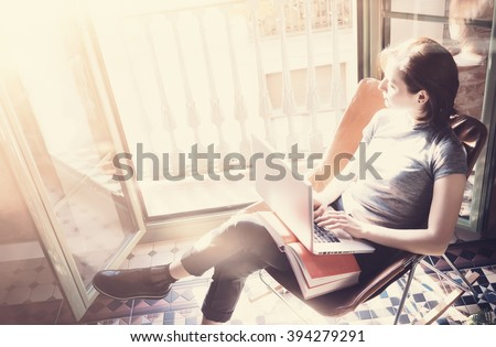 Photo young girl sitting leather armchair in modern building and use laptop wireless internet. Studying at the University, working, preparing exams. Using book, computer. Sunlight effect. Horizontal  - stock photo