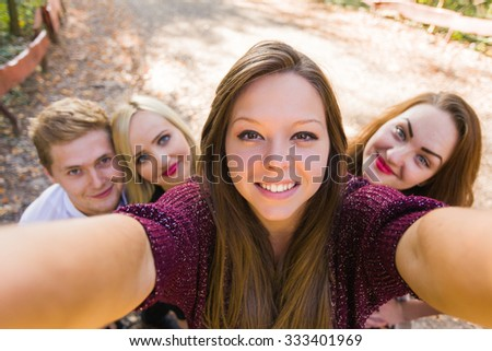 Photobomb performed by her good friends while she took a selfie for social network - the camera's point of view. - stock photo