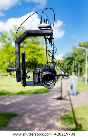 photocamera on the platform close-up and blurred videographer, use camera crane in the park at summer day - stock photo