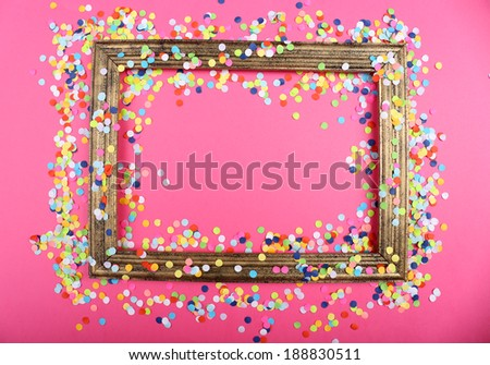 Photoframe with confetti on pink background - stock photo