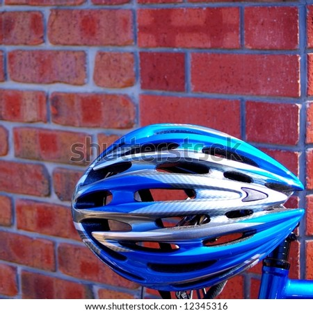 """Photograph featuring a cyclist's helmet hanging on a bike, resting on a brick wall, along the """"Riesling Trail"""" in the Clare Valley Wine Region of South Australia. - stock photo"""