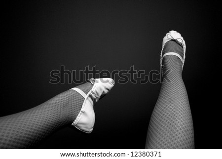 Photograph featuring a dancer's legs & feet, with teal fishnet tights and pink ballet shoes. - stock photo