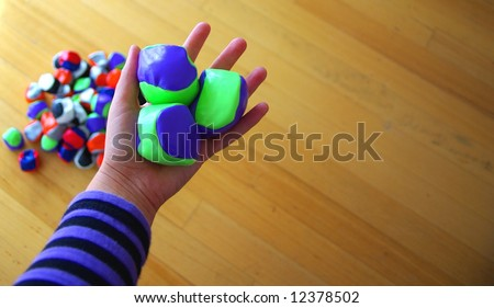 Photograph featuring a pile of juggling balls/hacky sacks, with a juggler's hand holding three of them (Australia). - stock photo
