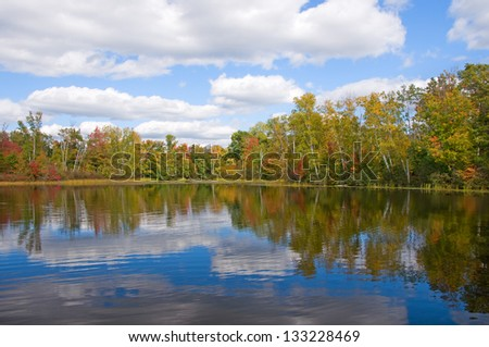 Photograph of a beautiful northwoods lake in early Autumn showing the beginning of changing colors, reflected in the water and accentuated by an amazing sky. - stock photo