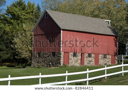 Photograph of a beautiful well maintained country barn set on a rolling midwestern landscape.