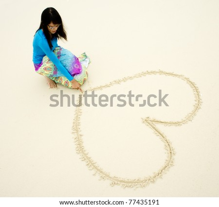 Photograph of a beautiful woman draw love shape on beach during holiday - stock photo