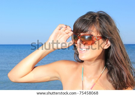 Photograph of a beautiful woman with sunglasses  posing and laughing at the beach