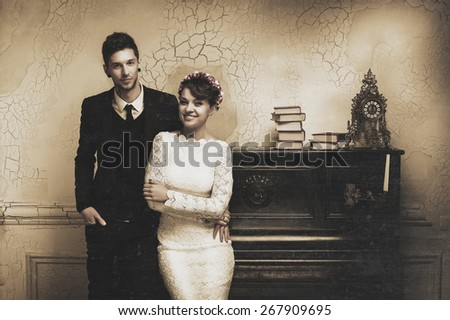 photograph of a beautiful young couple, the bride and groom standing near the old upright piano with a candelabra. photo Sepia - stock photo