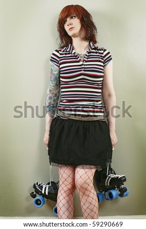 Photograph of a bored roller derby girl holding her skates and waiting against a wall. - stock photo