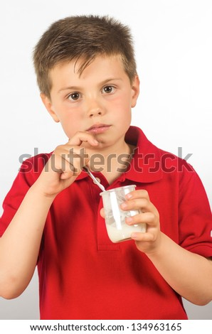 photograph of a child eating yogurt over white background