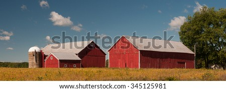 Photograph of a couple of barns or outbuildings of a farm beneath the harvest skies of early autumn.