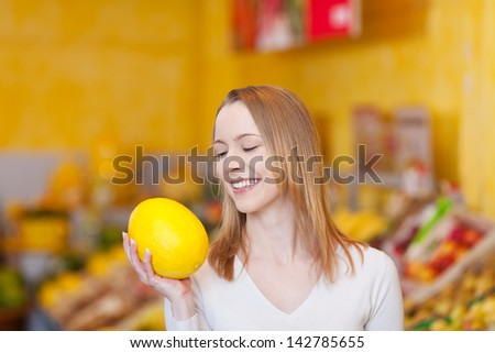 Photograph of a cute young female buying a melon. - stock photo
