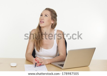 Photograph of a female business executive looking upset while working on a project, isolated on white background.