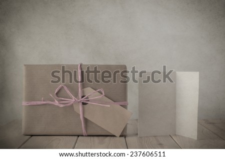 Photograph of a gift box wrapped in brown paper, tied in with pale pink raffia ribbon, with blank parcel tag label.  Beside is a blank greeting card on an old planked wooden table. Vintage style. - stock photo