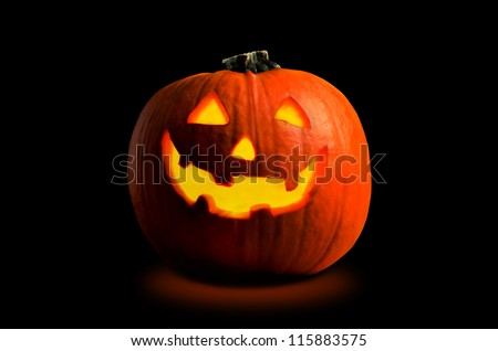 Photograph of a Halloween pumpkin (Jack O' Lantern), with carved face, lit by candlight from the inside on a black background with orange glow beneath. - stock photo