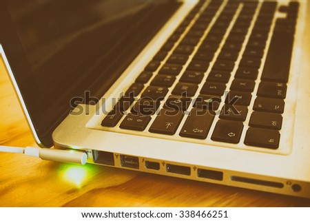 Photograph of a laptop keyboard charging battery on a wood table - stock photo