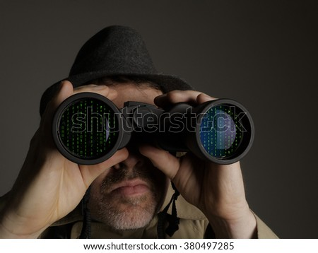 Photograph of a man in trench coat and hat looking through binoculars at computer code. - stock photo