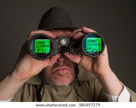 Photograph of a man in trench coat and hat looking through binoculars at silly text messages. - stock photo