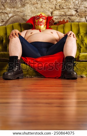 Photograph of a Mexican wrestler or Luchador sitting on a green couch waiting for his match to begin.