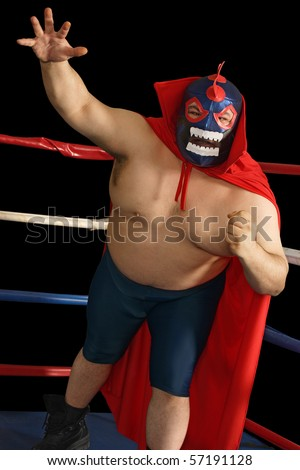 Photograph of a Mexican wrestler or Luchador standing in a wrestling ring. - stock photo