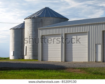Photograph of a modern steel garage and two silos on a working farm. - stock photo