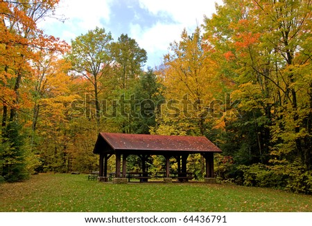 Photograph of a park setting in Wisconsin, with the beautiful green of fall grass, a red roofed shelter and all surrounded by the changing and pleasing colors of autumn. - stock photo