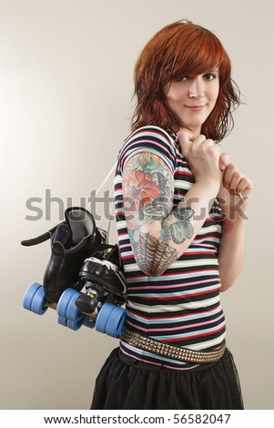 Photograph of a roller derby girl holding her skates by the laces. Attached property release is for arm tattoos. - stock photo