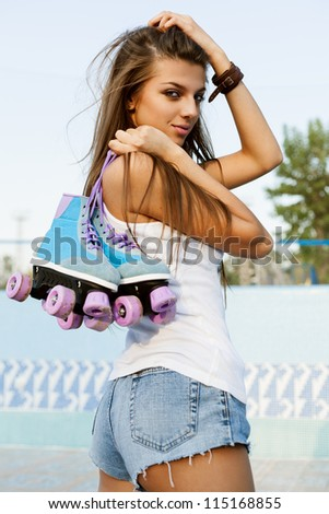 Photograph of a roller derby sexy woman holding her skates by the laces, outdoors - stock photo