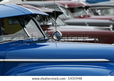 photograph of a row of classic cars in mint condition, shining chrome and highly polished finish - stock photo