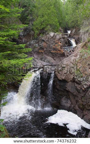 Photograph of a series of whitewater waterfalls crashing through a rocky gulch along the northshore of Lake Superior in late summer. - stock photo