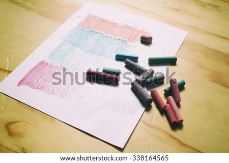 Photograph of a sheet of paper and color chalks in a retro style on a wood table