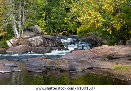 Photograph of a small waterfalls in a wild and remote area of the northwoods of Wisconsin, taken during the early Autumn as the colors are beginning to change. - stock photo