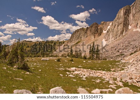 Photograph of a spectacular view in the Medicine Bow Mountain Range of Wyoming, with rocky field, beautiful cliffs and wonderful summer sky. - stock photo