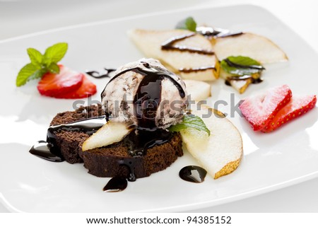 Photograph of a tasty dessert with chocolate cake ice cream and pear