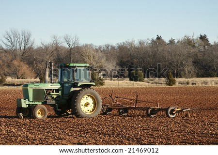 Photograph of a tractor in a plowed Oklahoma field. - stock photo