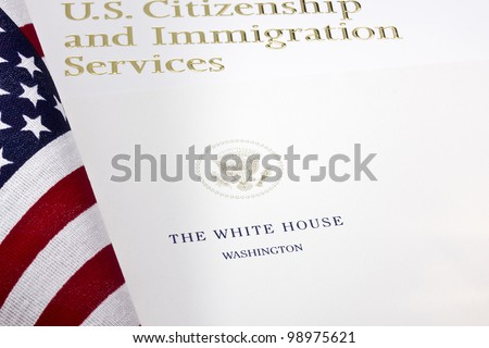 Photograph of a U.S. Department of Homeland Security logo under a paper with the White House seal. - stock photo
